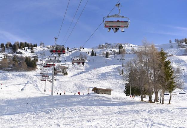 Impianti di risalita sotto il cielo blu e sopra la pista da sci Foto Premium