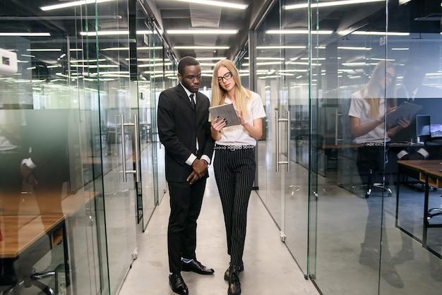 Impiegati di concetto maschii e caucasici femminili africani con il pc della compressa che sta al corridoio di ufficio vuoto e che discute nuovo progetto. Foto Premium