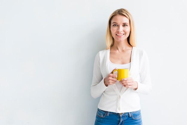 Impiegato biondo che tiene tazza su fondo bianco Foto Gratuite