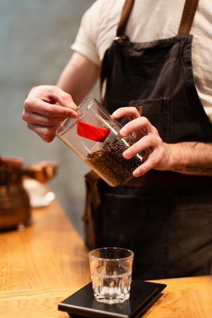 Impiegato della caffetteria che produce caffè Foto Gratuite