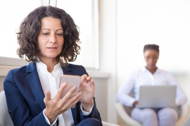 Impiegato di ufficio femminile con il web di navigazione delle cellule Foto Gratuite