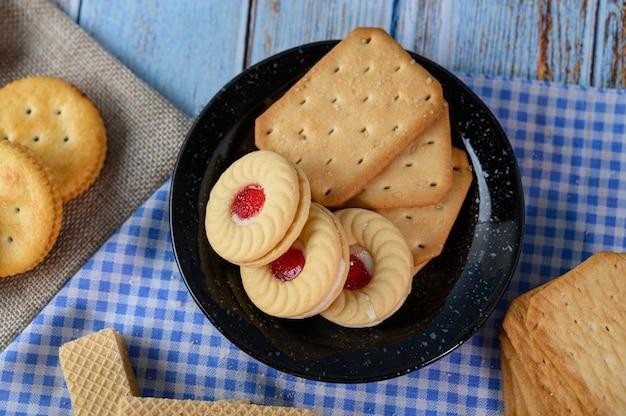 Impila molti tipi di biscotti su un piatto e metti su un tavolo di legno. Foto Gratuite