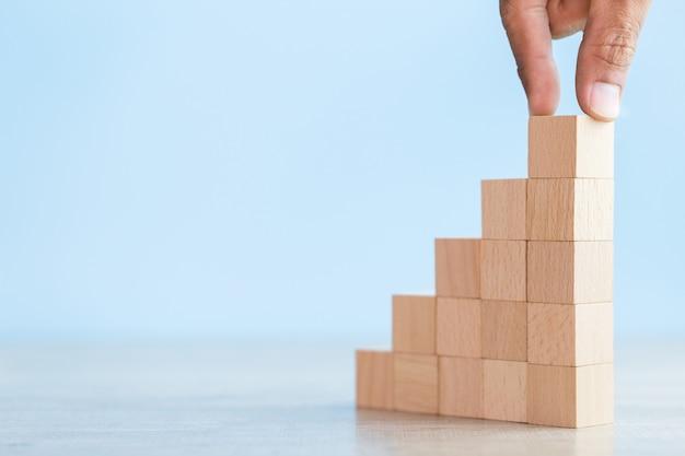 Impilando blocchi di legno in gradini, concetto di successo della crescita aziendale Foto Premium
