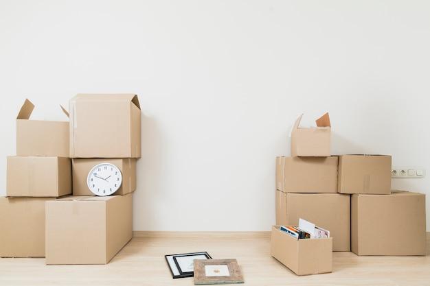 Impilati di spostare le scatole di cartone con orologio e cornice contro il muro bianco Foto Gratuite