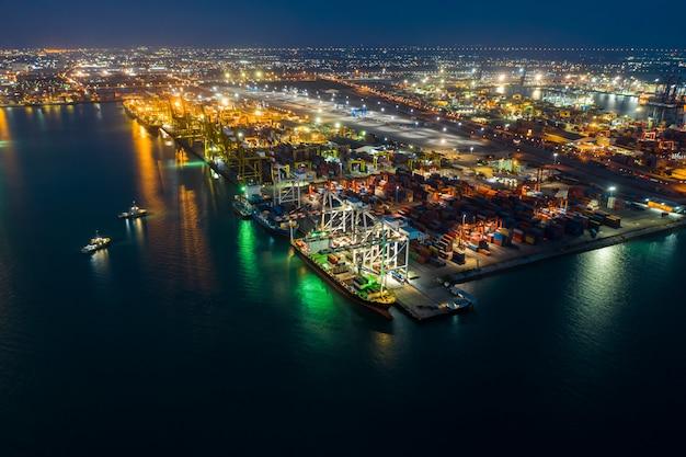Importazione internazionale ed esportazione esportando container marittimi e stazione di carico in tailandia alla vista aerea di notte Foto Premium