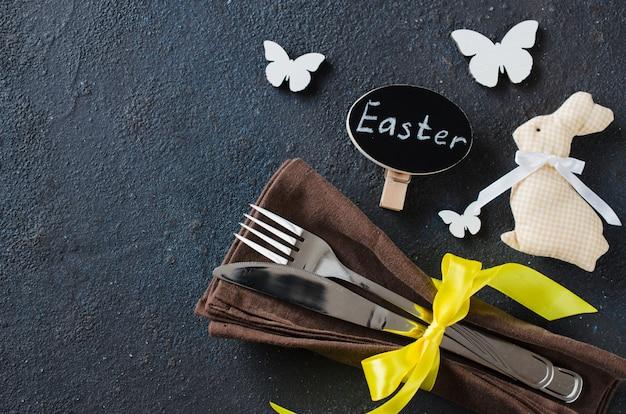Impostazione del tavolo festivo per le vacanze cena di pasqua sul tavolo scuro. Foto Premium