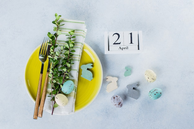 Impostazione del tavolo festivo per le vacanze di pasqua. concetto di carta di vacanza cattolica di primavera. calendario 21 aprile Foto Premium