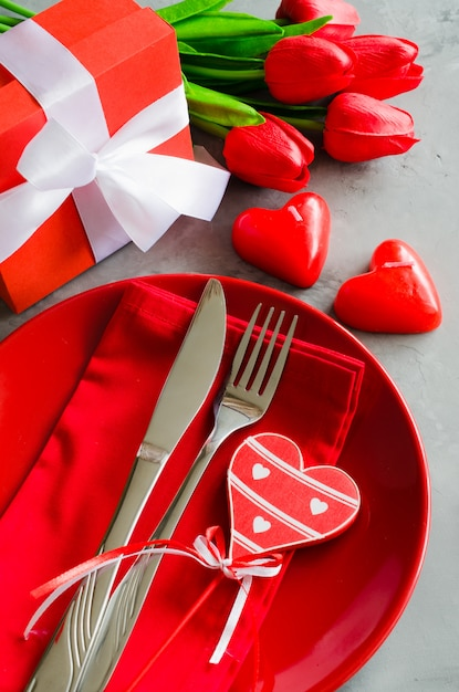 Impostazione del tavolo festivo per san valentino con confezione regalo e tulipani. Foto Premium