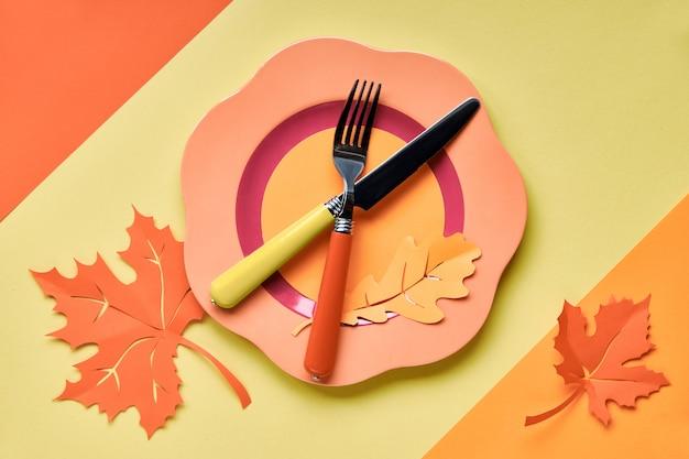 Impostazione del tavolo per la celebrazione autunnale. luminoso piatto di plastica su carta gialla con carta foglie d'autunno Foto Premium