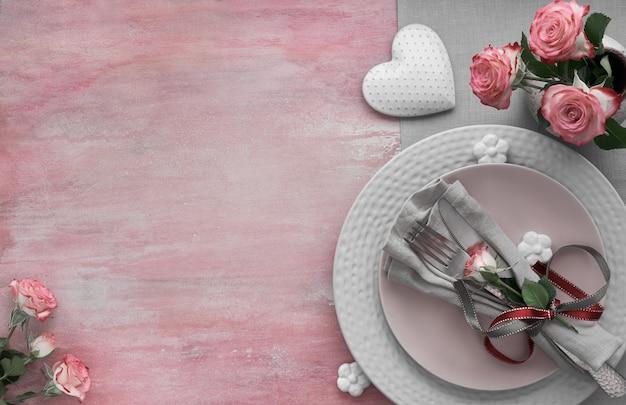 Impostazione del tavolo per san valentino, compleanno o anniversario, vista dall'alto su superficie rosa chiaro, copia-spazio Foto Premium