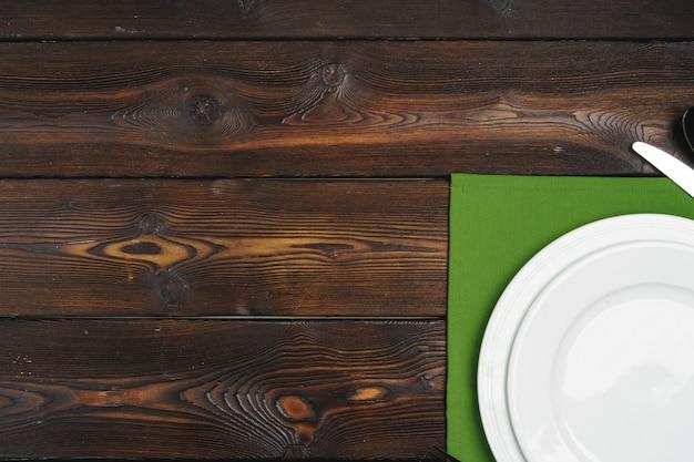 Impostazione della tabella con piastre su fondo di legno scuro Foto Premium