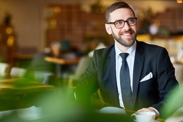 Imprenditore bello che lavora dal caffè Foto Gratuite