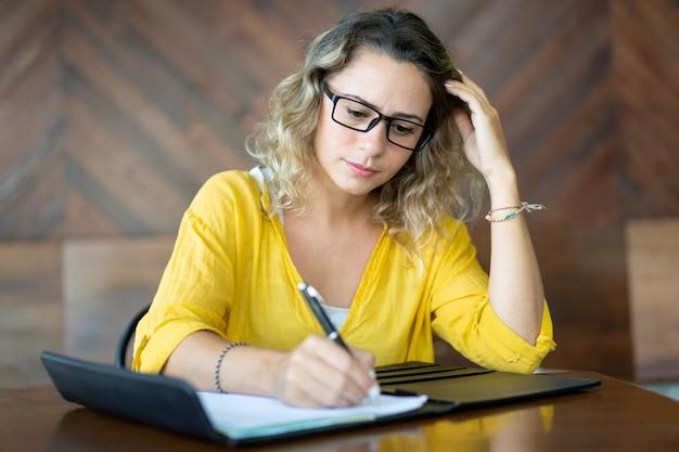 Imprenditore femminile serio che scrive le idee per il progetto startup Foto Gratuite