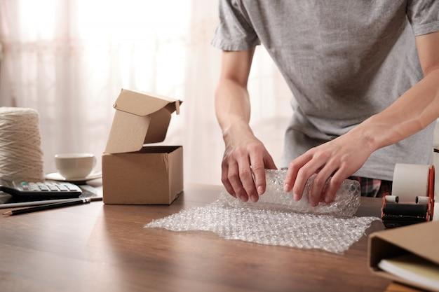 Imprenditore giovane startup che imballa prodotti in plastica antiurto per l'invio al cliente Foto Premium