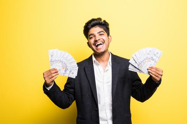 Imprenditore indiano di successo con il vestito classico disponibile delle banconote del dollaro che esamina macchina fotografica con il sorriso a trentadue denti mentre stando contro la parete gialla Foto Gratuite