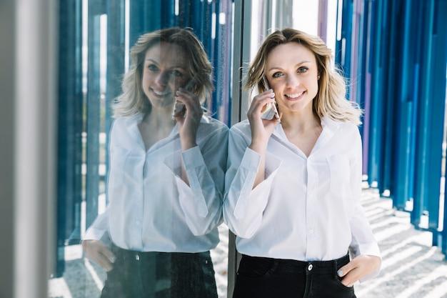 Imprenditrice facendo telefonata accanto a windows Foto Gratuite