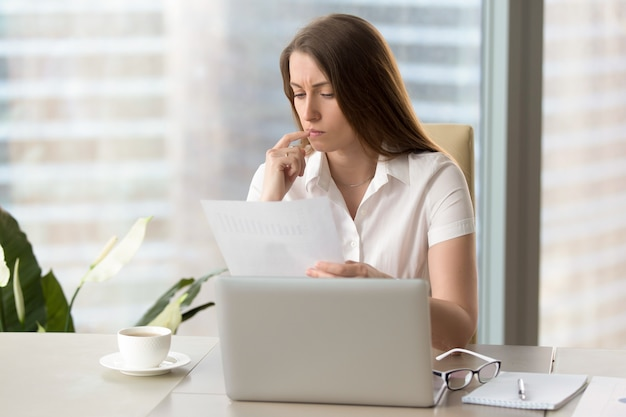 Imprenditrice focalizzata analizzando il documento, tenendo relazione finanziaria sul posto di lavoro Foto Gratuite