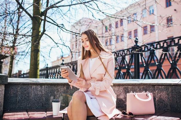 Imprenditrice in pausa nel parco. giovane donna professionale di affari che per mezzo del computer della compressa all'aperto. modello femminile caucasico. Foto Premium