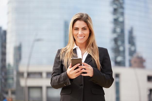 Imprenditrice parlando al cellulare in ambiente urbano Foto Premium