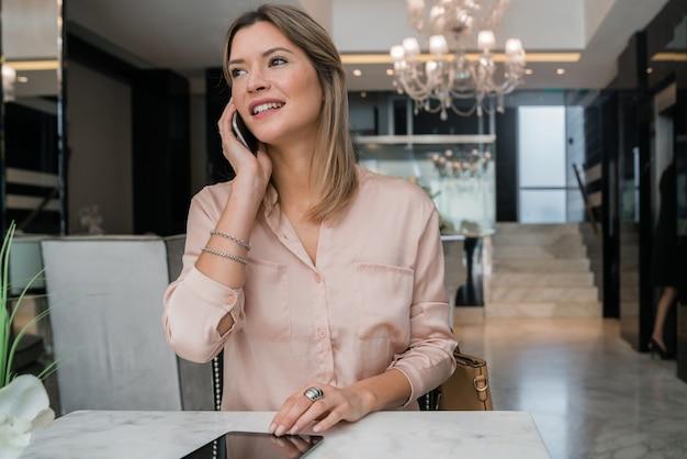 Imprenditrice parlando al telefono nella hall dell'hotel. Foto Premium