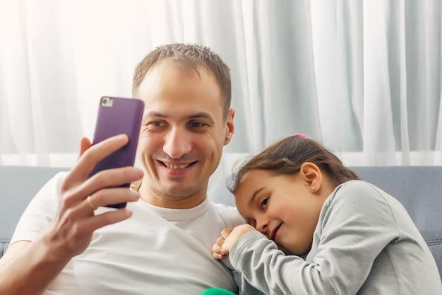 In the evening father e little daughter seduti su un divano smartphone. Foto Premium