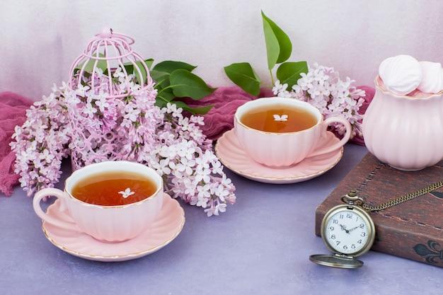 In una gabbia decorativa rosa rosa lilla, due tazze di tè, un libro e un orologio da tasca Foto Premium