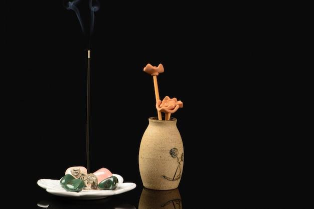Incenso con elefante e pietre e vaso in ceramica su fondo nero Foto Premium