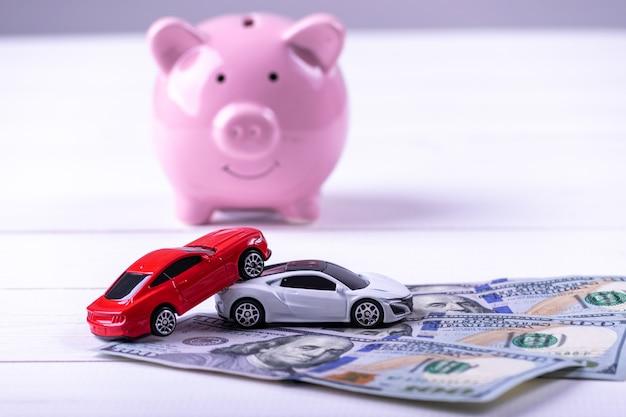 Incidente stradale sulla banconota dei dollari con il porcellino salvadanaio. concetto di assicurazione Foto Premium