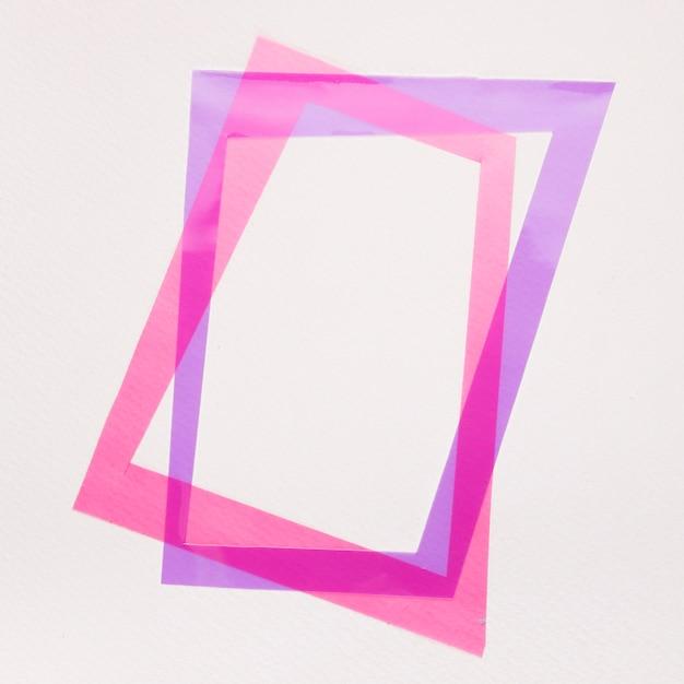 Inclinare la cornice viola e rosa su sfondo bianco Foto Gratuite
