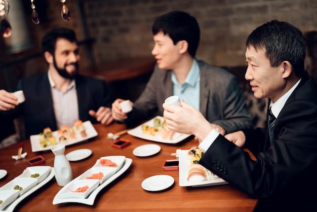 Incontro con uomini d'affari giapponesi in giacca e cravatta nel ristorante. Foto Premium