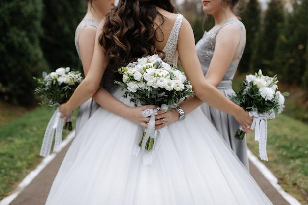 Indietro di una sposa e damigelle con mazzi di nozze bianche eustoma all'aperto Foto Gratuite