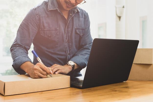 Indirizzo di scrittura di uomo d'affari delle pmi sul pacco con labtop sul tavolo. Foto Premium