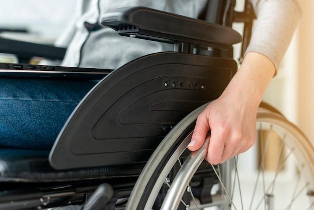 Individuale del primo piano che si tiene per mano sulla sedia a rotelle Foto Gratuite