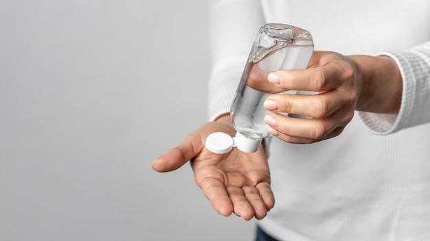 Individuo del primo piano facendo uso del gel di pulizia per le mani Foto Gratuite