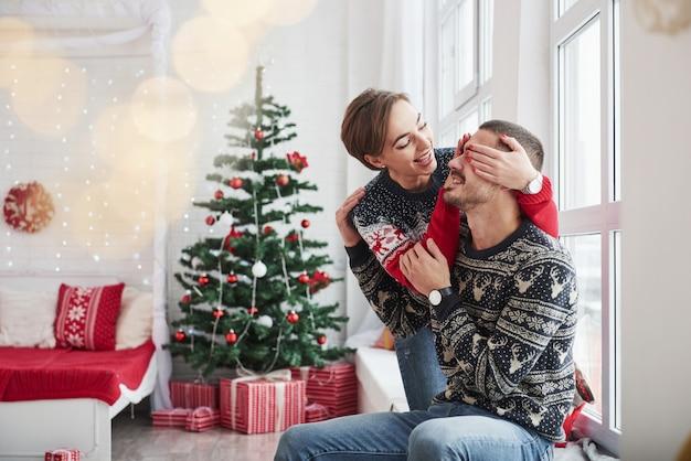 Indovina quale regalo ti farò. i giovani felici si siede sul davanzale della finestra nella stanza con decorazioni natalizie Foto Premium