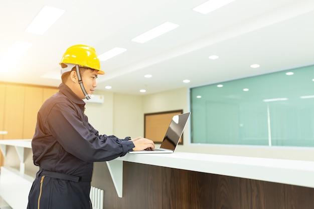 Industrial engineer in hard hat wearing safety jacket utilizza laptop touchscreen. Foto Premium