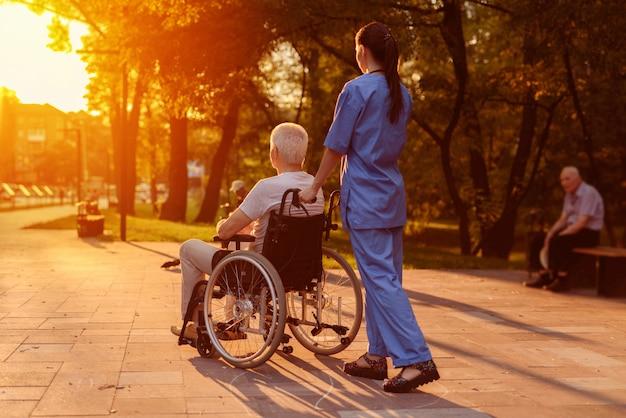 Infermiera e vecchio che si siede in sedia a rotelle a guardare il tramonto Foto Premium