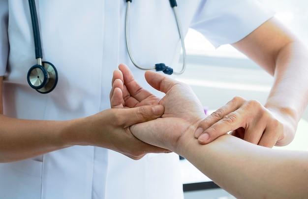 Infermiere che controlla l'impulso del paziente, impulso medico del controllo a mano. concetto medico e sanitario. Foto Premium
