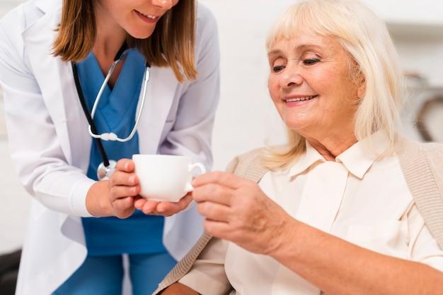 Infermiere che dà tè al primo piano della donna anziana Foto Gratuite