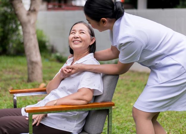 Infermiere che si tiene per mano alla donna asiatica anziana con la malattia di alzheimer, il pensiero positivo, felice e sorridente, ciao e sostiene il concetto Foto Premium