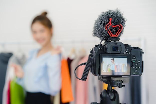 Influencer online di blogger femminile della moda asiatica che tiene i sacchetti della spesa e molti vestiti Foto Gratuite