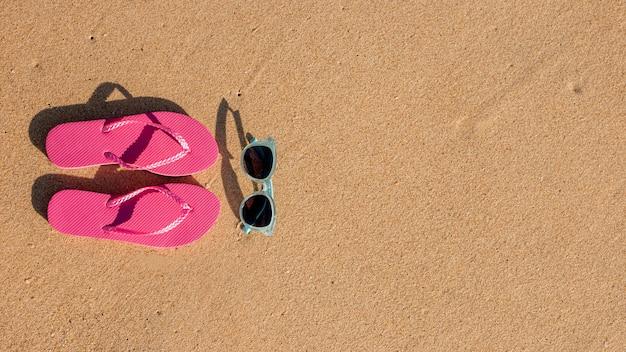 Infradito e occhiali da sole sulla sabbia Foto Gratuite