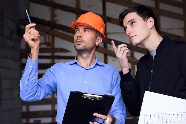 Ingegnere architetto che indossa un casco arancione sul luogo di lavoro che spiega i piani del progetto al cliente Foto Premium