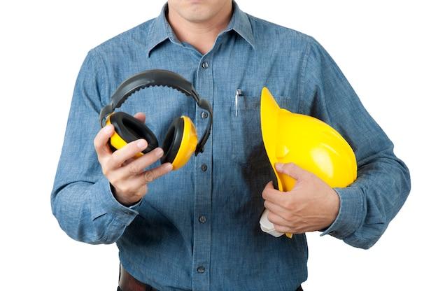 Ingegnere astuto il lavoratore indossa una maglietta blu e tiene in mano un elmetto giallo e un manicotto giallo Foto Premium