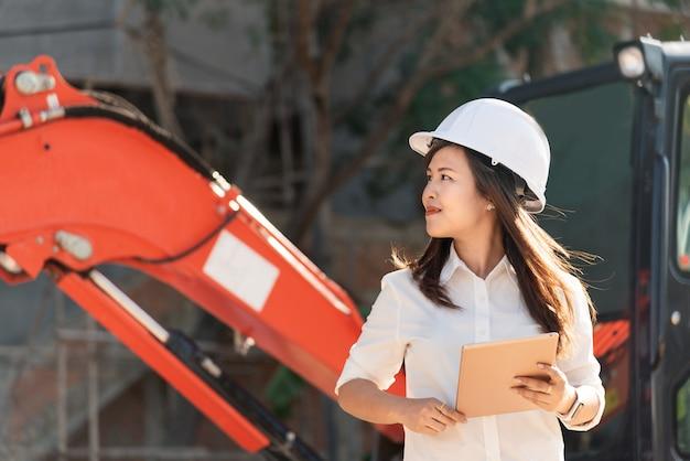 Ingegnere civile della donna asiatica con il cantiere di visita bianco del casco di sicurezza. Foto Premium