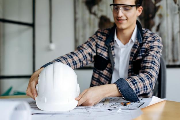 Ingegnere con cappello duro nelle sue mani lavorando in ufficio Foto Premium