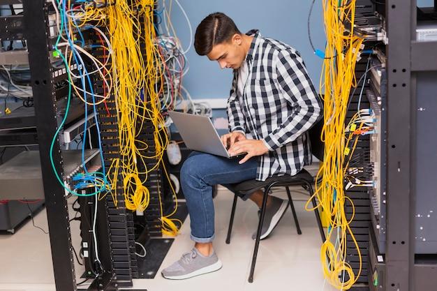 Ingegnere di rete con una possibilità remota del computer portatile Foto Gratuite