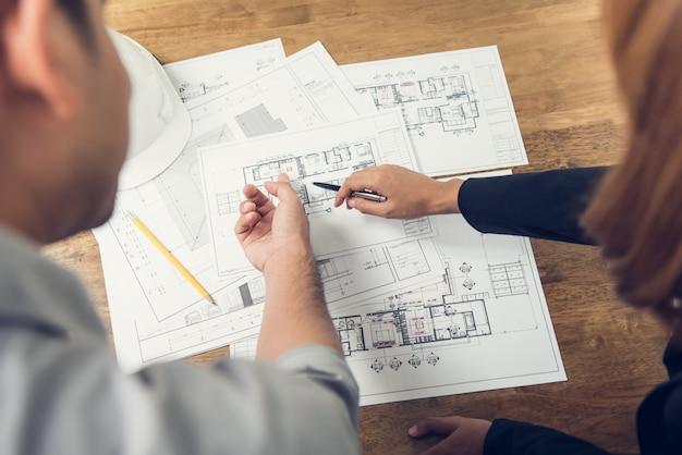Ingegnere e architetto discutendo sulla progettazione del layout del piano di energia elettrica Foto Premium