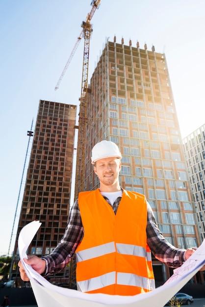 Ingegnere edile di vista di angolo basso medio del colpo che esamina i piani Foto Gratuite