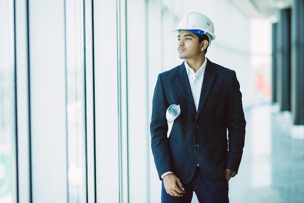 Ingegnere maschio indiano dell'appaltatore del sito con il casco che tiene la carta della stampa blu che cammina al cantiere Foto Gratuite